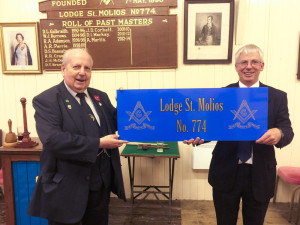 Brother Jim Coles presents RWM Tim Keen with the new sign for the outside of the Lodge building
